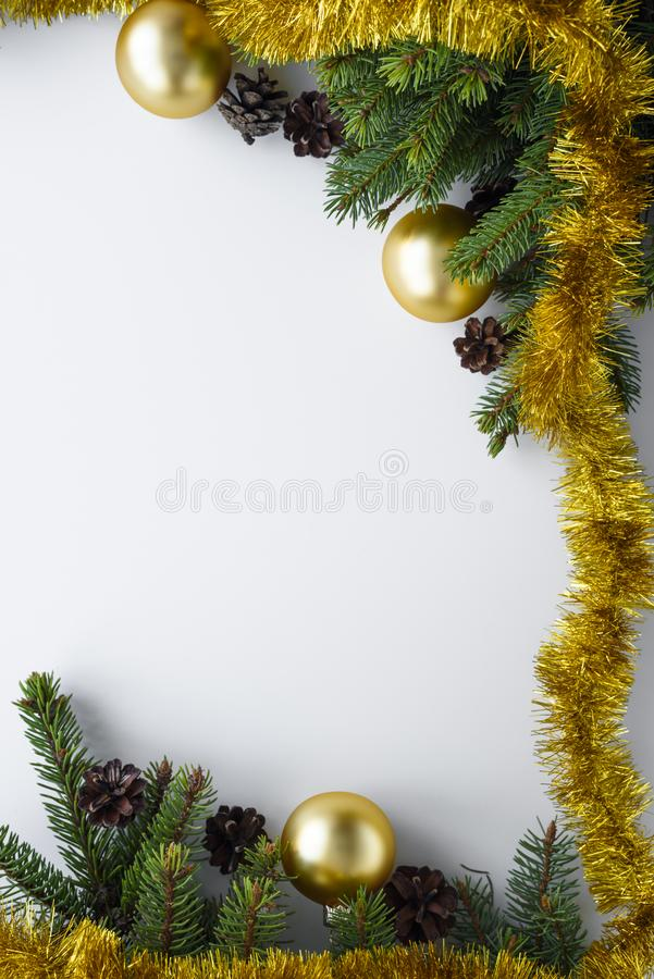 Festive ornaments as a christmas frame with copy space. Spruce tree branches, cones, gold baubles and tinsel. Vertical greeting. Festive ornaments as a christmas royalty free stock photography