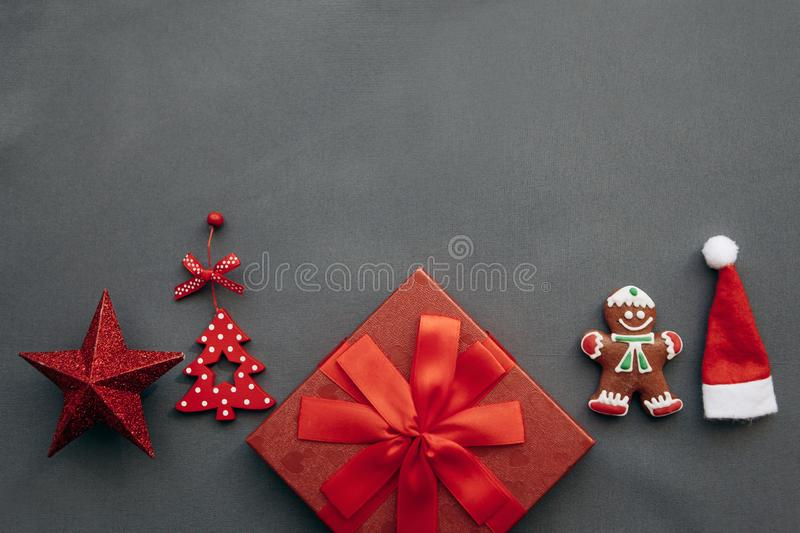 A festive red box with a bow and next to it a variety of Christmas decorations, toys and food. stock photography