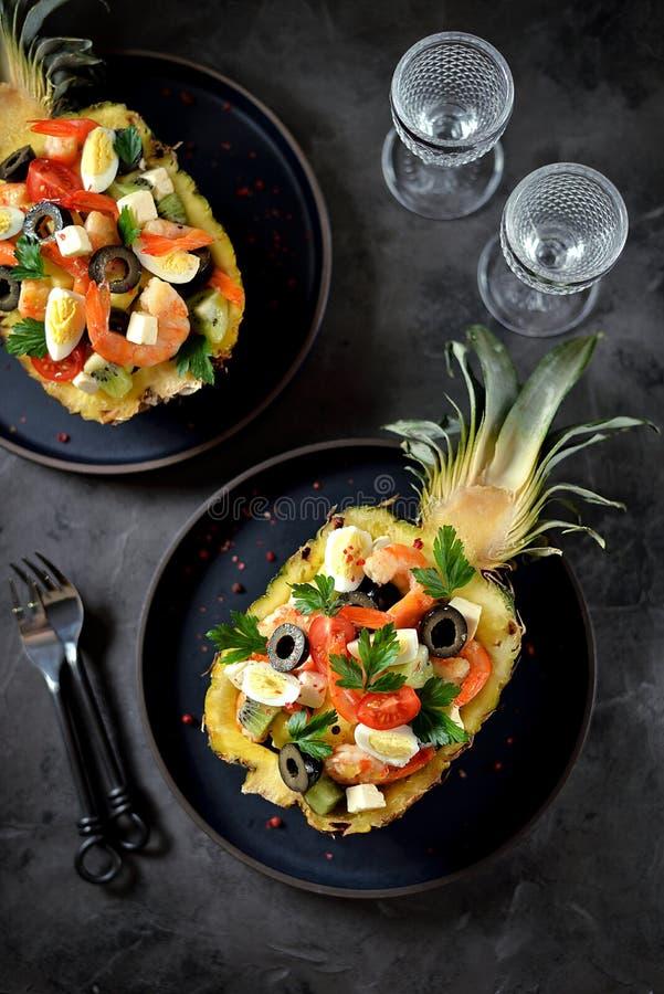 Festive salad of shrimp, kiwi, olives, soft cheese, quail eggs, cherry tomato in pineapple plates. Christmas background. royalty free stock photos