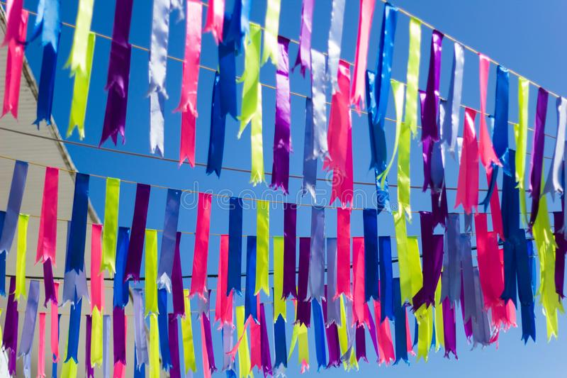 Festive satin ribbons. Decorating the street in front of the blue sky stock image
