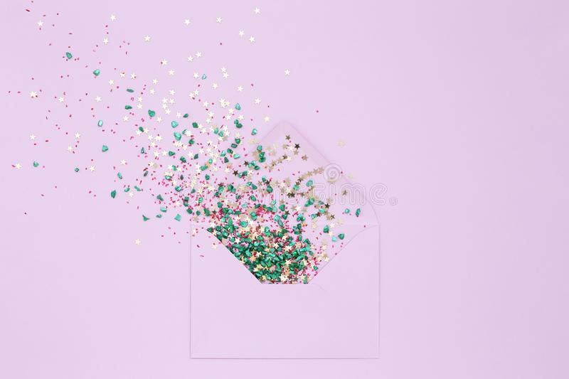 Festive Sequins explosion from envelope on lilac royalty free stock photos