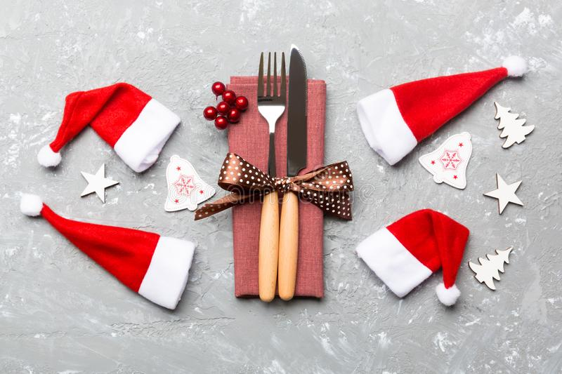 Festive set of fork and knife on cement background. Top view of new year decorations and santa clothes and hat. Close up of royalty free stock photography