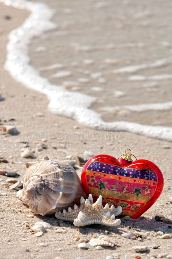 Christmas ornament and shells at the beach. A festive setting of a christmas ornament, a whelk and a starfish at the beach with a wave at low tide along royalty free stock photography