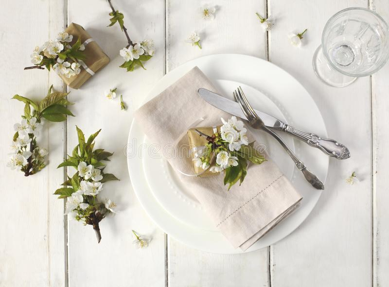 Festive spring table setting with pear blossom flowers royalty free stock image