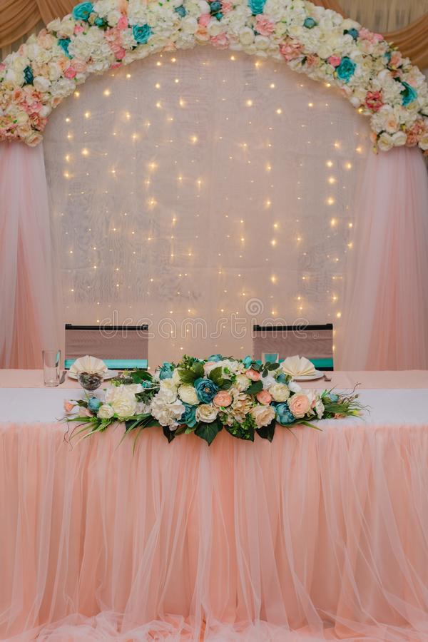 Festive table for the bride and groom decorated with cloth and flowers royalty free stock photos