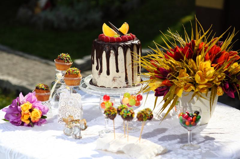 A festive table decorated with birthday cake with flowers and sweets. A table with a cake for the birthday of the child. Birthday party for children royalty free stock photos