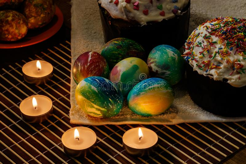 Festive table for Easter. There are two Easter cakes on the table, several Easter eggs are lying, candles are burning stock photography