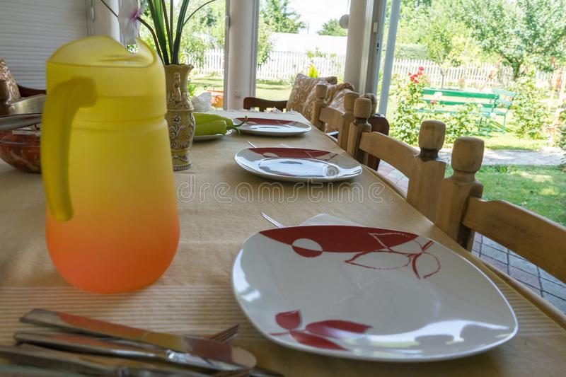 Festive table served dishes and decorated. Lunch in the open air. Orange pitcher of water and flowers. Salad and food in the royalty free stock images