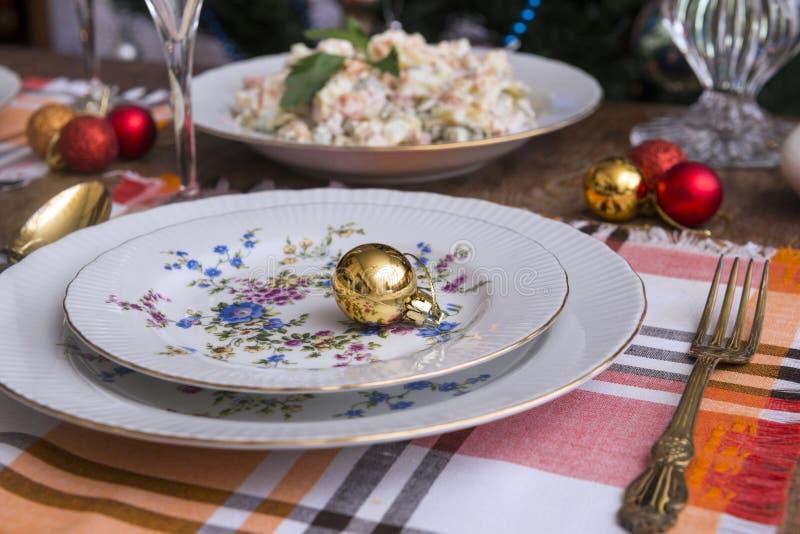 Festive table set, plates, fork, Olivier salad, Christmas balls, napkins. Food, new year, Christmas royalty free stock photography