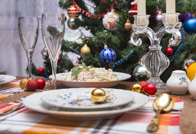 Festive table set, plates, fork, Olivier salad, red, Golden Christmas balls, napkins, food, new. Festive table , plates, fork, Olivier salad, red, Golden royalty free stock image