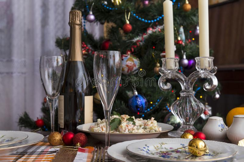 Festive table set, plates, fork, Olivier salad, red, Golden Christmas balls, napkins, food, new. Festive table set, plates, fork, Olivier salad, red, Golden royalty free stock images