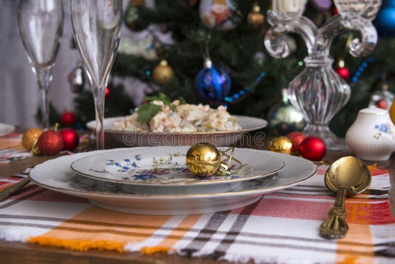 Festive table set, plates, fork, Olivier salad, red, Golden Christmas balls, napkins, food, new year, Christmas, glasses,. Christmas tree, candlestick stock photos