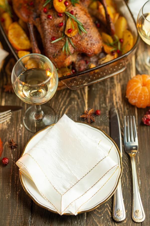 Festive table setting bowls and cutlery, glasses of wine against a background of baked duck.  stock photo