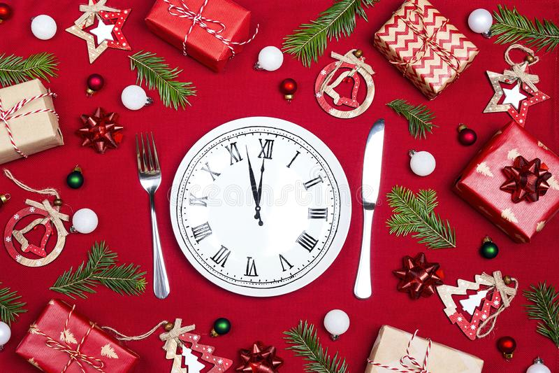 Festive table setting with dish clock and Christmas decorations stock image