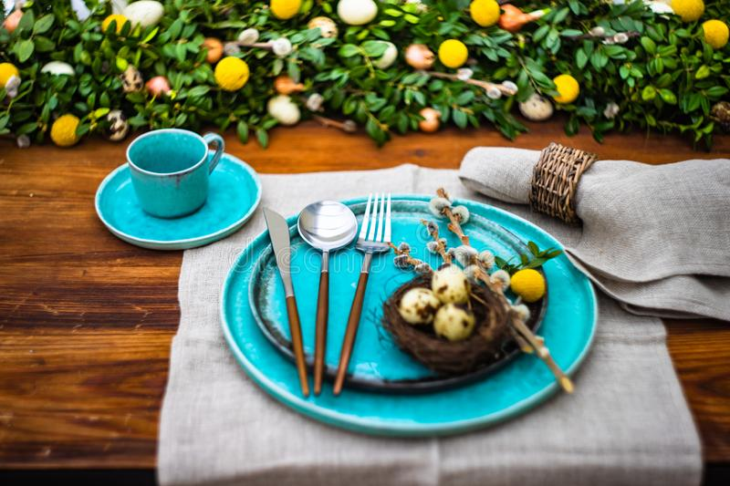 Easter table setting. Festive table setting for Easter holiday dinner decorated with flowers and eggs royalty free stock photo
