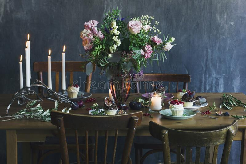 The festive table setting with flower bouquet, candles and dess royalty free stock image