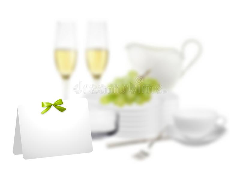 Festive table setting. In the foreground, a white card with a green bow. In the background serving items. There is a place for text. White background help to royalty free stock image