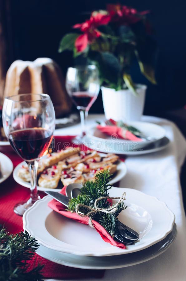 Festive table setting for holiday dinner with dishes and red wine at home near Christmas tree. Family together Christmas. Celebration concept. Natural stock image