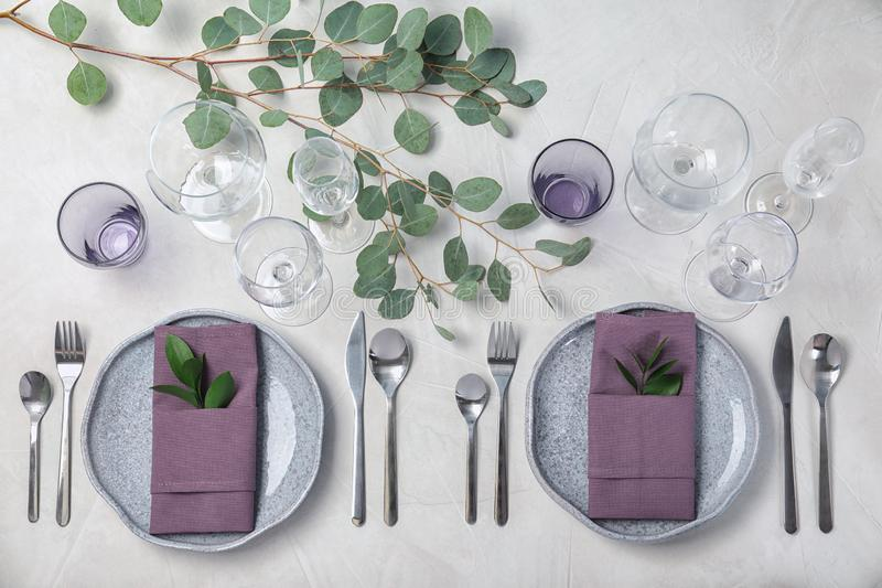 Festive table setting with plates, cutlery and napkins on light background. Flat lay stock photos