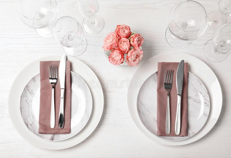Festive table setting with plates, cutlery and napkins on wooden background. Flat lay stock photos