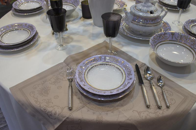 Festive table setting, purple white set. White linen tablecloth, purple plate cutlery. Deep plates glasses spoons forks knives royalty free stock photo