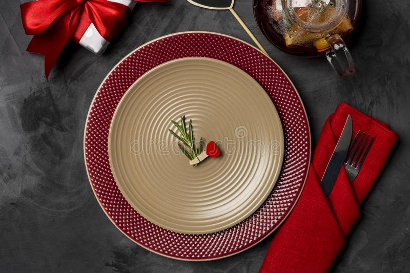 Festive table setting for Valentine`s Day with fork, knife and heart pin with rosemary at plates on a black table. Top view. Festive table setting for Valentine` royalty free stock photos