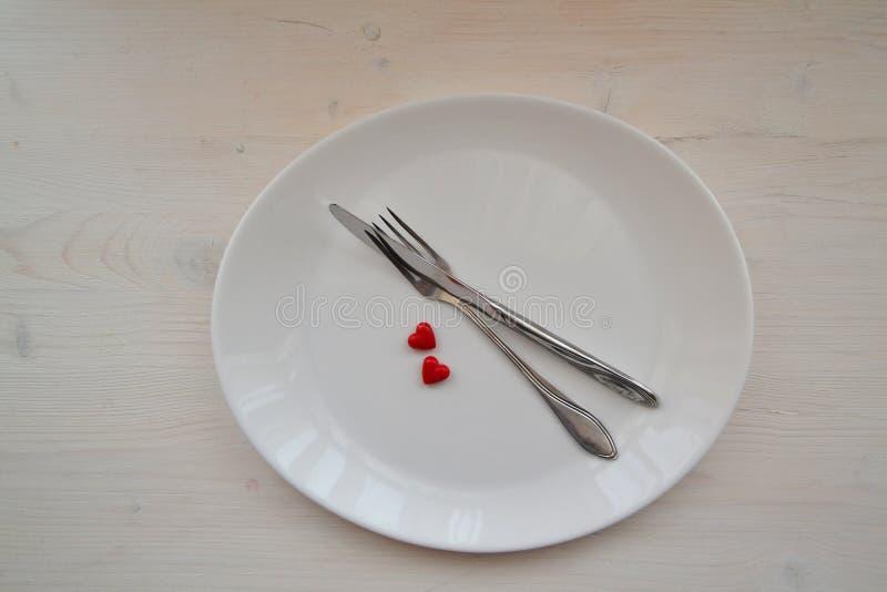 Festive table setting voor Valentijnsdag met vork, mes en hart op een witte houten tafel Bovenaanzicht stock afbeelding
