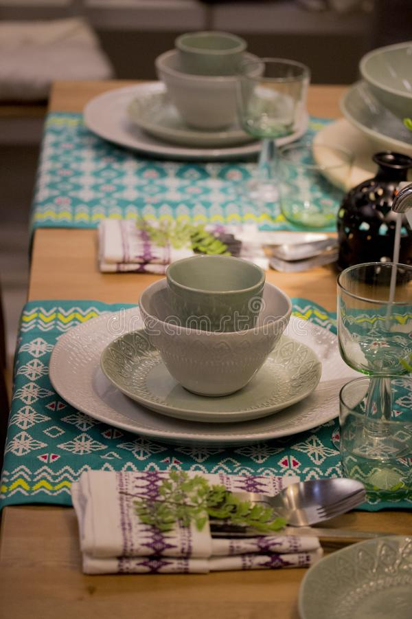 Festive table setting in white and green tones. Plates wine glasses on ethnic napkin with ornament stock image