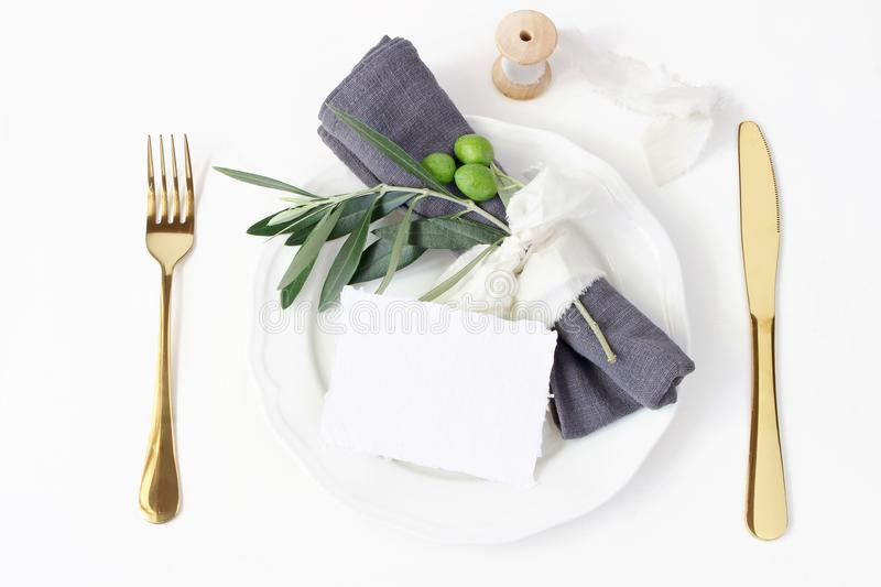 Festive table summer setting. Golden cutlery, olive branch, linen napkin, porcelain dinner plate and silk ribbon on royalty free stock image