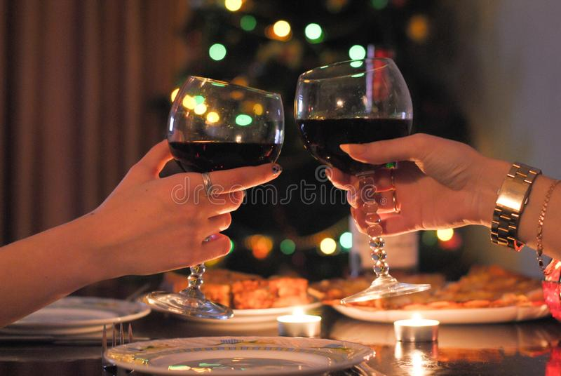 Festive table and two glasses of wine in hand. Photo is suitable for stories about holidays and vacations stock image