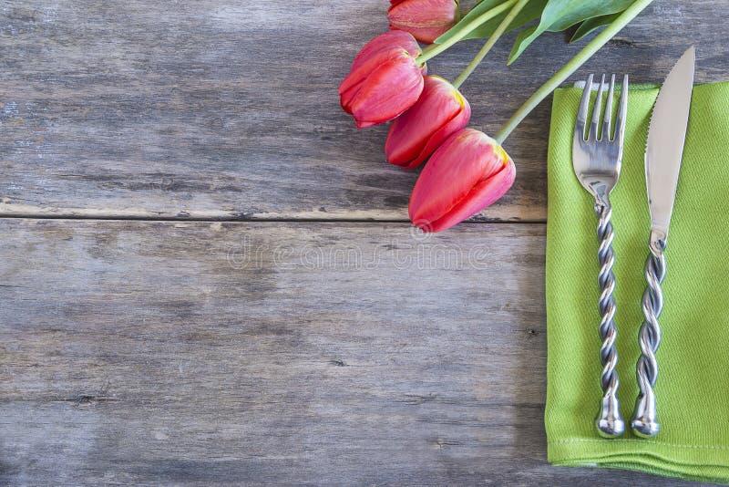 Festive tafel-setting met prachtige messenmakerswerk op groene servet en bouquet van rode tulpen op oude niet-verfhouten achtergr royalty-vrije stock foto