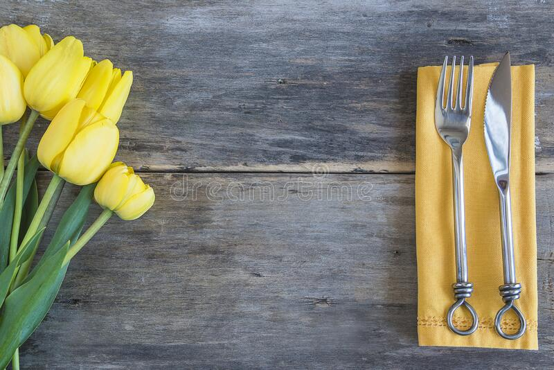 Festive tafel setting met stelletje gele tulpen en mooie messenmakerswerk op oude niet-verfhouten achtergrond stock afbeeldingen
