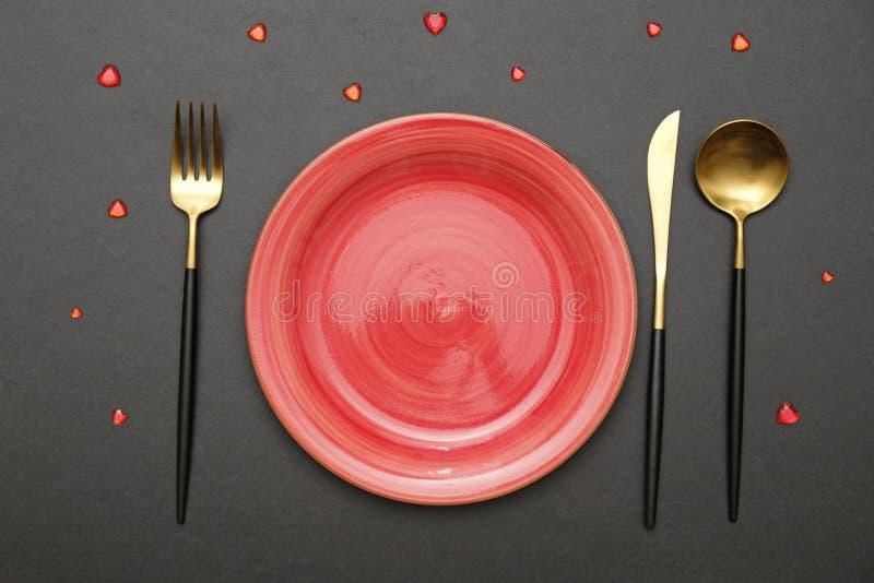 Festive tafel setting voor Valentijnsdag met vork, mes en harten op een zwarte tafel Bovenaanzicht royalty-vrije stock afbeelding