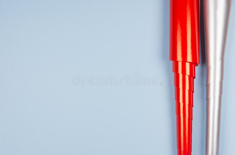 Festive template for design and text of bright glossy red and metallic silver wrapping paper rolls on pastel blue background. Festive template for design and stock photography