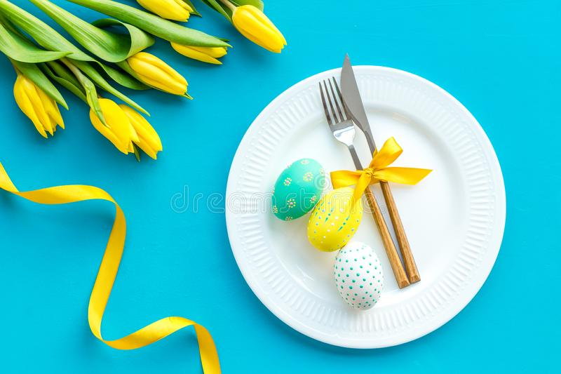 Festive traditional Easter dinner concept. Tableware, painted eggs, tulips flowers on blue table top view royalty free stock photos