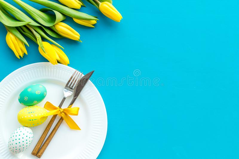 Festive traditional Easter dinner concept. Tableware, painted eggs, tulips flowers on blue table top view copy space royalty free stock photo