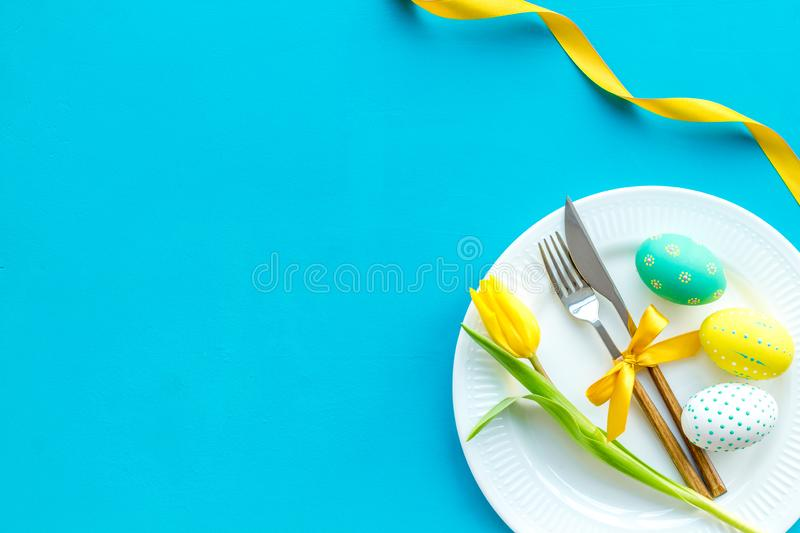 Festive traditional Easter dinner concept. Tableware, painted eggs, tulips flowers on blue table top view copy space royalty free stock images