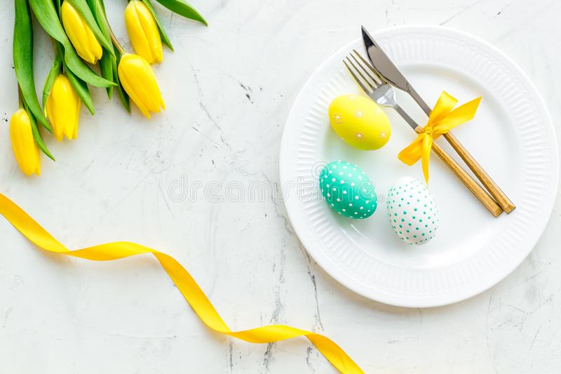 Festive traditional Easter dinner concept. Tableware, painted eggs, tulips flowers on white stone table top view stock photo