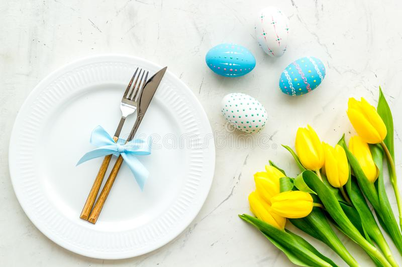 Festive traditional Easter dinner concept. Tableware, painted eggs, tulips flowers on white stone table top view stock image