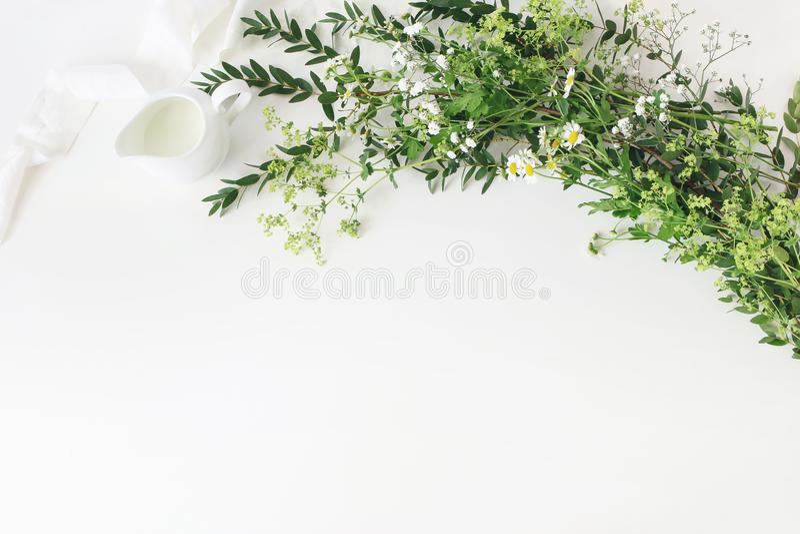 Festive wedding, birthday table scene with eucalyptus parvifolia, silk ribbon, wild meadow flowers and milk pitcher on royalty free stock image