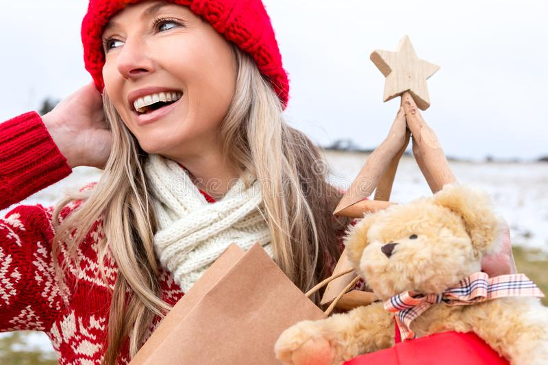 Festive woman carring Christmas things... Christmas snowy backdrop royalty free stock photo