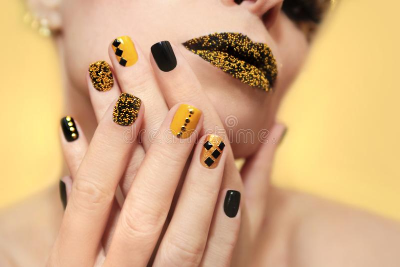 Festive yellow black manicure and makeup. stock image