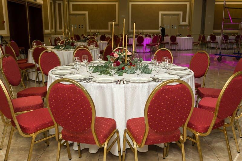 Festively που διακοσμείται γύρω από τον πίνακα συμποσίου στο εστιατόριο Τα φρέσκα λουλούδια είναι χρυσά κεριά και κόκκινες καρέκλ στοκ εικόνα