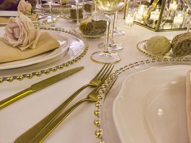 Festively decorated wedding table with tablecloth and rose flowers and golden cutlery to celebrate the party.  stock photo
