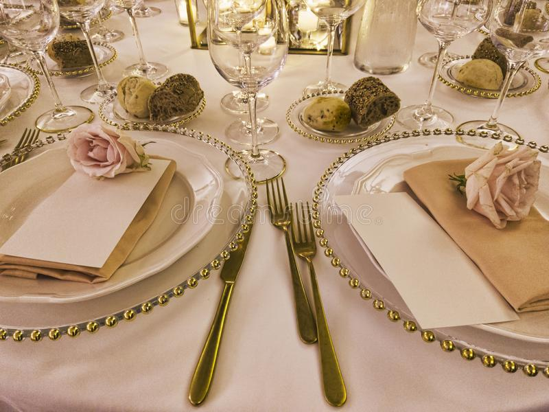 Festively decorated wedding table with tablecloth and rose flowers and golden cutlery to celebrate the party.  stock images