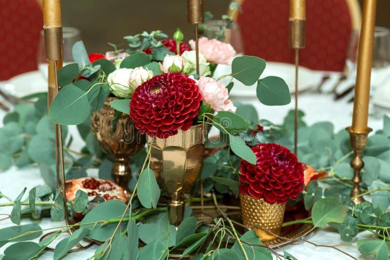 Festively dekorerad banketttabell i restaurangen Nya blommor ?r guld- stearinljus och r?da stolar och granatr?tt dyrt rikt arkivbild
