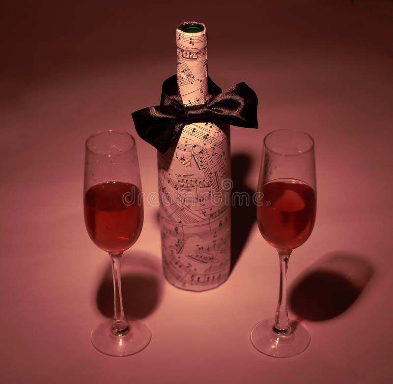 Festively dekorerad flaska av vin och två exponeringsglas royaltyfria foton