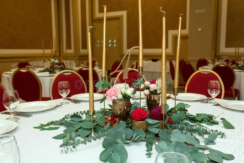Festively dekorerad rund banketttabell i restaurangen Nya blommor ?r guld- stearinljus och r?da stolar dyrt rikt royaltyfria foton