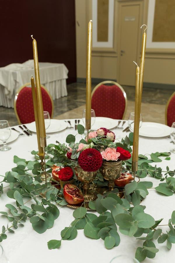 Festively dekorerad rund banketttabell i restaurangen Nya blommor ?r guld- stearinljus och granatr?tt och r?da stolar dyrt royaltyfria foton