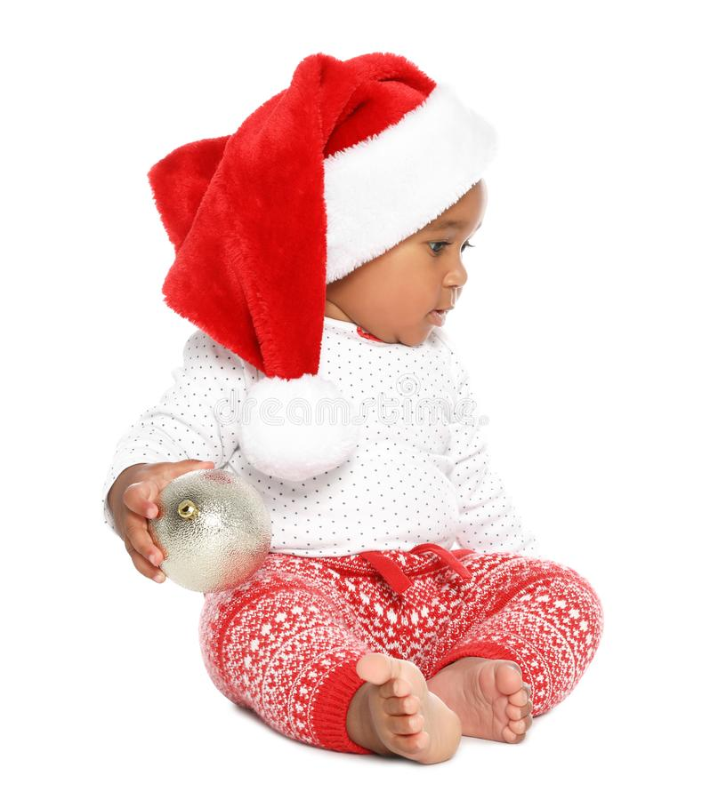 Festively dressed African-American baby with Christmas ball on background royalty free stock photo
